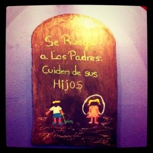 Cartel de madera en el Mesón Xoquin (Viveiro, Galicia): Se ruega a los padres cuiden de sus hijos